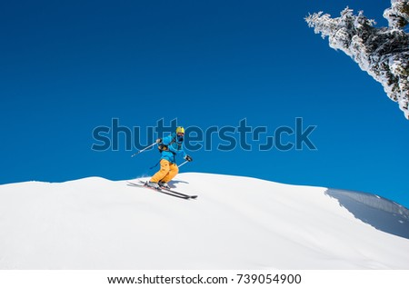 Freeride skier riding down the slope in the mountains copyspace powder snow movement motion active lifestyle seasonal concept #739054900