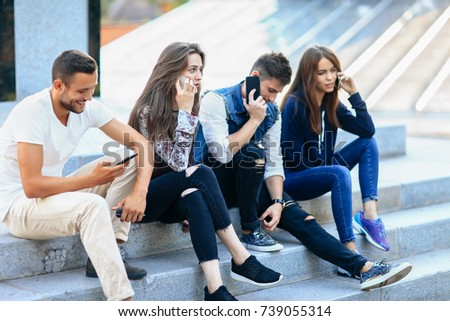 Four young people sitting on stairs and using mobile phones. Two women and one man talking on smartphone and one guy browsing. Modern life and technology concept #739055314