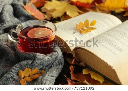 Autumn, fall  leaves, cup of tea, opened book  and warm scarf on wooden table. Seasonal, book reading, Sunday relaxing, teatime and still life concept. Selective focus. #739121092