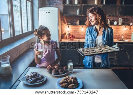 Attractive young woman and her little cute daughter are eating cakes and cookies on kitchen and drinking milk. Having fun together while enjoying freshly baked pastries. #739143247