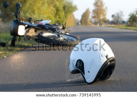 Photo of helmet and motorcycle on road, the concept of road accidents Royalty-Free Stock Photo #739145995