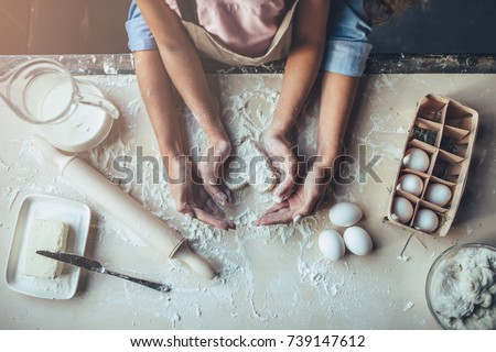 Cropped image of attractive young woman and her little cute daughter are cooking on kitchen. Having fun together while making cakes and cookies. Top view of mom with daughter making dough heart. Royalty-Free Stock Photo #739147612