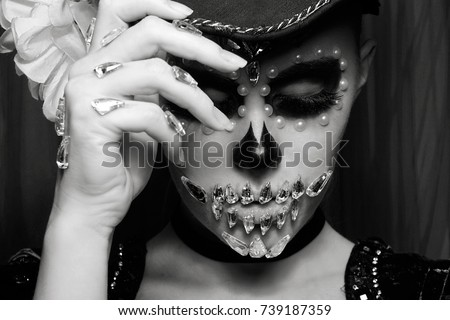 Black and white photo.Girl with black hat.Halloween skeleton woman.Woman in day of the dead mask skull face art. Halloween face art .Portrait of zombie woman.