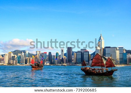 Hong Kong skyline cityscape, Tourist junk boat at Victoria Harbor in evening Royalty-Free Stock Photo #739200685
