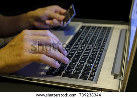 Hands of someone typing card number on a computer keyboard for shopping online. #739238344