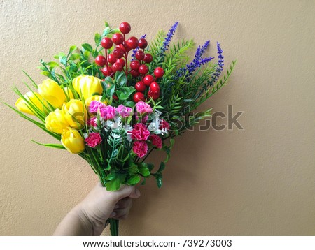 Hand holding Bouquet of artificial flowers colorful selective focus on brown wall background #739273003