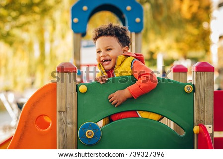 Adorable little 1-2 year old toddler boy having fun on playground, child wearing orange hoody jacket and yellow vest  Royalty-Free Stock Photo #739327396