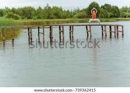 A man doing yoga on wooden pier at the lake #739362415