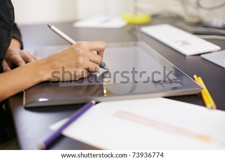closeup of female dressmaker sketching and drawing dresses with graphic tablet. Horizontal shape, side view