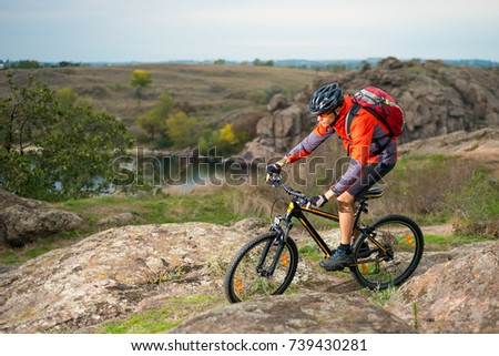 Cyclist in Red Riding the Bike on the Autumn Rocky Trail. Extreme Sport and Enduro Biking Concept. #739430281