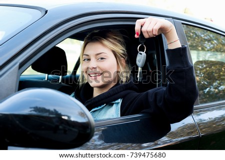 Girl sitting in her car and showing key #739475680