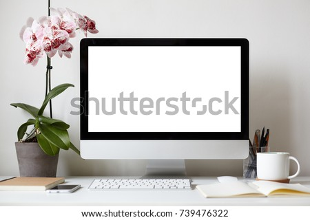Picture of modern personal computer with blank white copy space screen resting on desk with keyboard, orchid in pot, mug, cellular phone, copybooks and stationery items. Mock up of workplace #739476322
