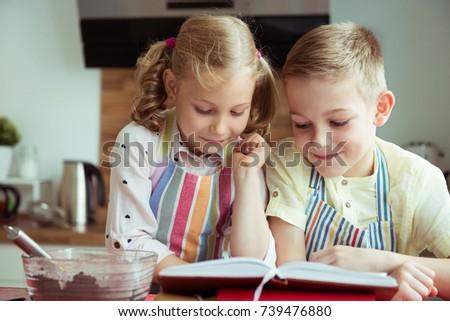 Two beautiful and happy children having fun exploring recept before preparing christmas cookies #739476880