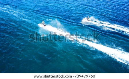 Aerial bird's eye view of jet skis racing in high speed competition in turquoise clear water sea #739479760