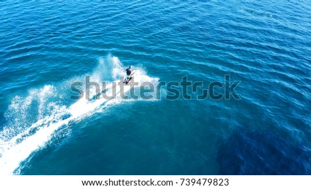 Aerial bird's eye view of jet ski cruising in high speed in turquoise clear water sea #739479823