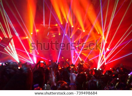 Rock concert background, large group of people enjoying party, having fun in night club in bright red laser light, active night life, music star performance #739498684