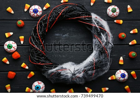 Halloween candy corns with eyes and spiders on wooden table #739499470