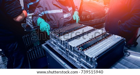 Charging the batteries of the elecric motor. Disassembling the battery of an electric vehicle engine. Car service Royalty-Free Stock Photo #739515940