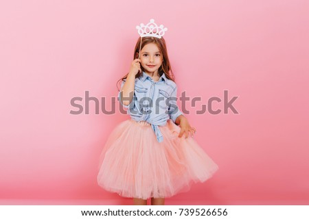 Cheerful little girl with long brunette hair in tulle skirt holding princess crown on head  isolated on pink background. Celebrating brightful carnival for kids, birthday party, having fun of cute kid #739526656
