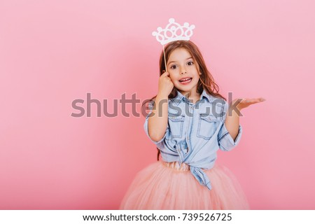 Joyful little girl with long brunette hair in tulle skirt holding princess crown on head isolated on pink background. Celebrating brightful carnival for kids, expressing positivity of birthday party #739526725