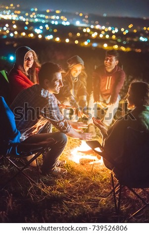 The happy people warming hands above the bonfire. evening night time #739526806