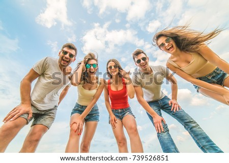 The happy people look to the camera on the background of clouds #739526851