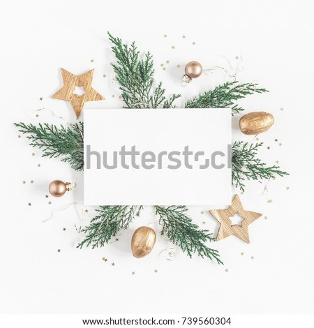 Christmas composition. Paper blank, christmas tree branches, golden decorations on white background. Flat lay, top view, copy space, square.