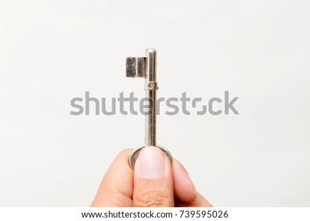 Hand holding the key Isolated on white background. Studio lighting. #739595026