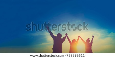 Silhouette of happy teamwork hold hands up as a business successful, business victory, achieve business goal Royalty-Free Stock Photo #739596511