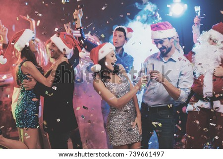 Young couple dancing with glasses of champagne in hands. Behind them dance their friends and a man dressed as Santa Claus. Against the background of colored smoke, confetti flies around. #739661497
