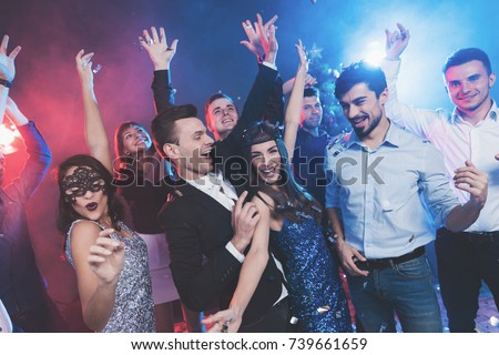 New Year party. Young couple dancing with glasses of champagne in hands. Against the background, young people's friends are dancing. Around fly confetti and there is white smoke. #739661659