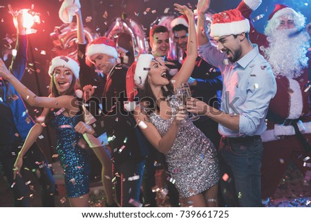 Young couple dancing with glasses of champagne in hands. Behind them dance their friends and a man dressed as Santa Claus. Against the background of colored smoke, confetti flies around. #739661725