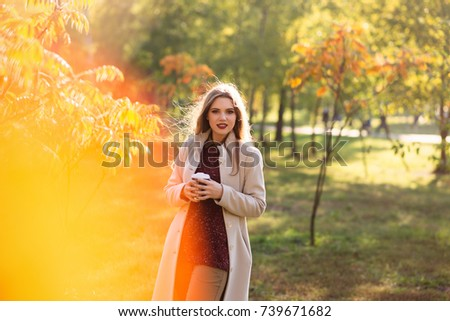 The girl with a cup of coffee in the autumn forest #739671682