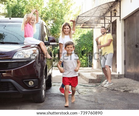 Happy family playing while washing car outdoors #739760890