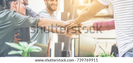 Young team putting hands up for new startup in creative office - Cheerful people giving strength motivation - Soft focus on woman with red pullover hand - Co-working and teamwork concept #739769911