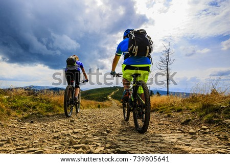 Cycling couple on cycle trail in autumn forest. Mountain biking in autumn landscape forest. Man and woman cycling uphill trail. #739805641