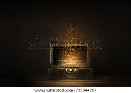 Glowing golden sparkles and stars rising from an old, opened wooden treasure chest. Darkly lit on a planked surface with black chalkboard background. #739844707