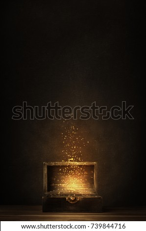 Glowing golden sparkles and stars rising from an old, opened wooden treasure chest. Darkly lit on a planked surface with black chalkboard background. #739844716