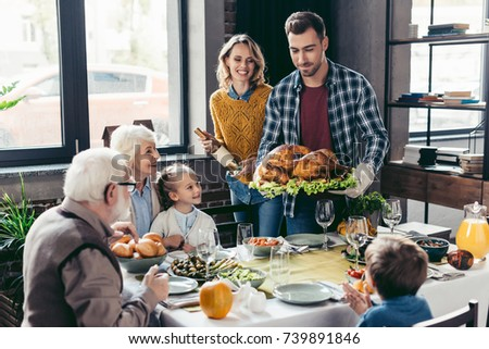 man with delicious turkey for holiday dinner with beautiful family #739891846