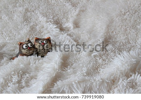 Figurines of enamored cats. Romantic image of cats on a fur cover. Couple in love.