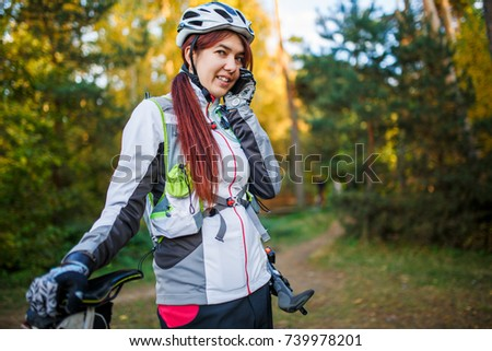 Image of girl with bicycle in helmet talking on phone #739978201