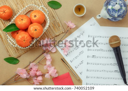 Top table view Chinese & Lunar new year with music sheet note paper concept background.space for creative design text or font.Essential item on the modern rustic brown wood at home office studio.  #740052109