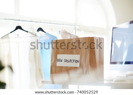 Paperbag named new collection on background of clothes on hangers #740052529