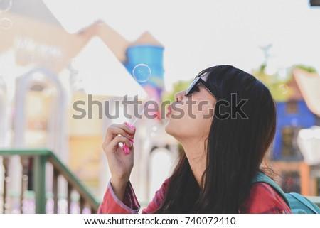Beautiful girl is playing soap bubble fun. #740072410