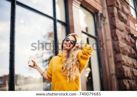 Pretty girl wearing sunglasses and bracelets smiling on the street. Outdoor portrait of laughing blonde young woman in mustard sweetshot standing near store.She holds coffee to go