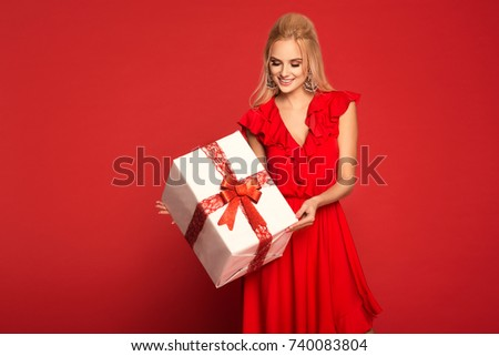 Beautiful young blonde woman in red dress holding a big present. Christmas photo, gifts. All red.  #740083804
