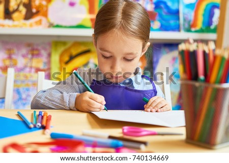 Portrait of adorable little girl  drawing pictures during art and craft class in pre-school
