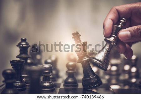 hand of businessman moving chess figure in competition success play. strategy, management or leadership concept  Royalty-Free Stock Photo #740139466