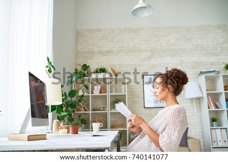 Side view portrait of modern young woman reading book at computer desk taking break from freelance work in home office #740141077