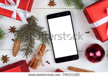 Close up of mobile smart phone with blank white screen for app presentation with Christmas decorations on wooden background, copy space. Flat lay, top view. Christmas application mock up template
